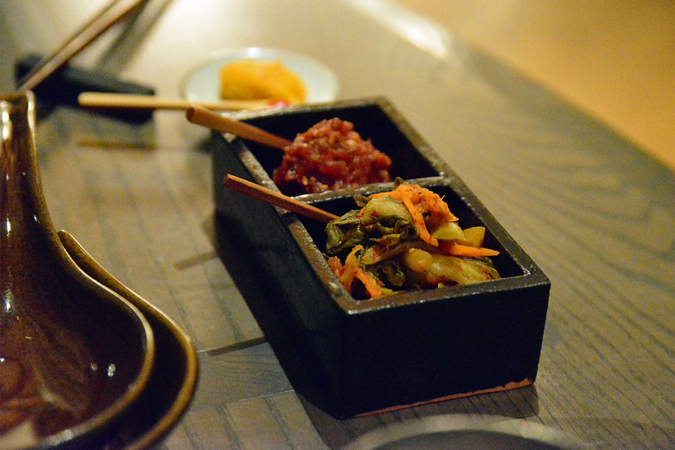 The donabe was accompanied by several small, unique ceramic pieces, each with a different condiment.