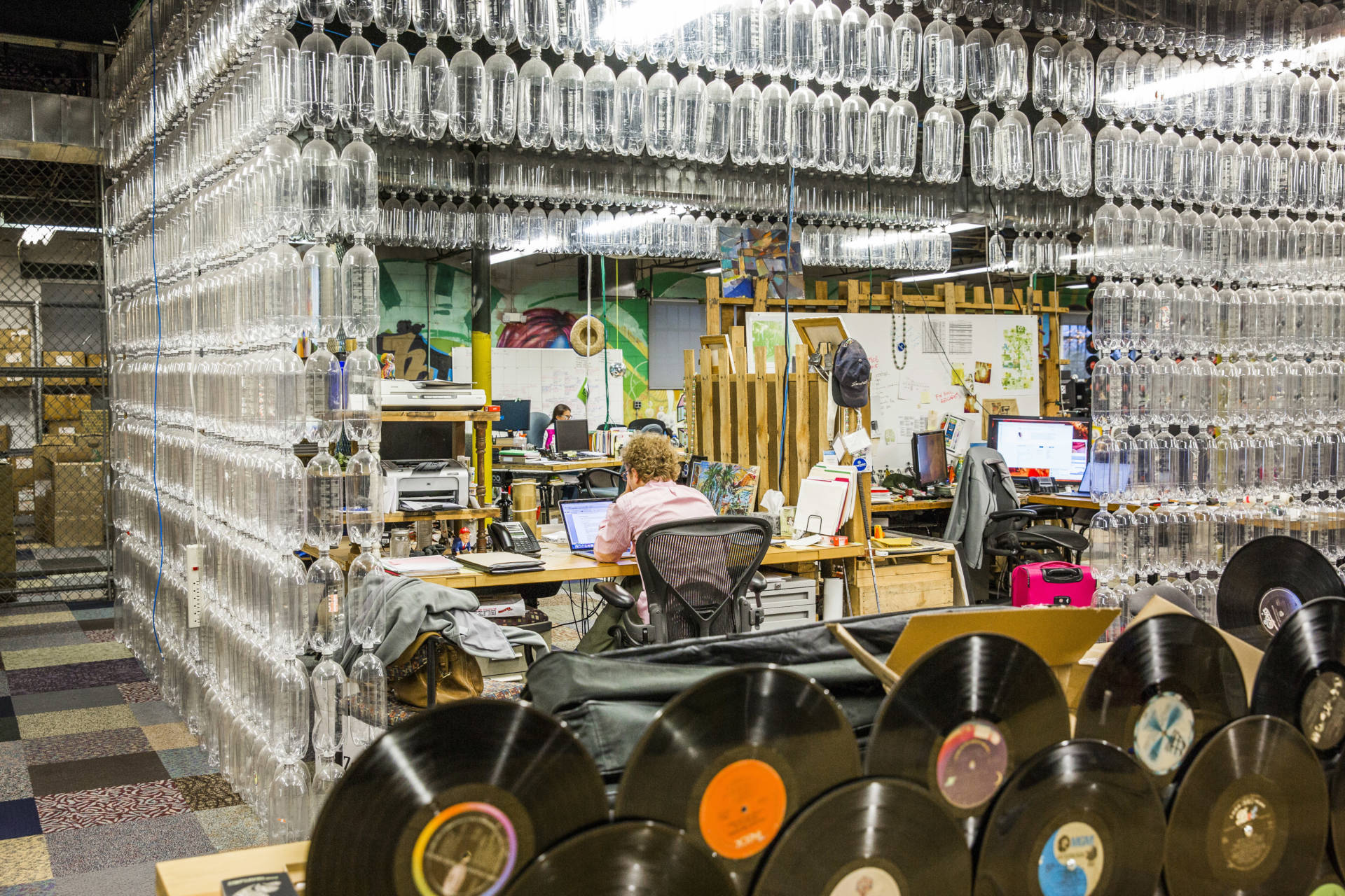 Plastic bottles surround an employee at a workstation inside recycling company TerraCycle's headquarters in Trenton, N.J., in 2017.