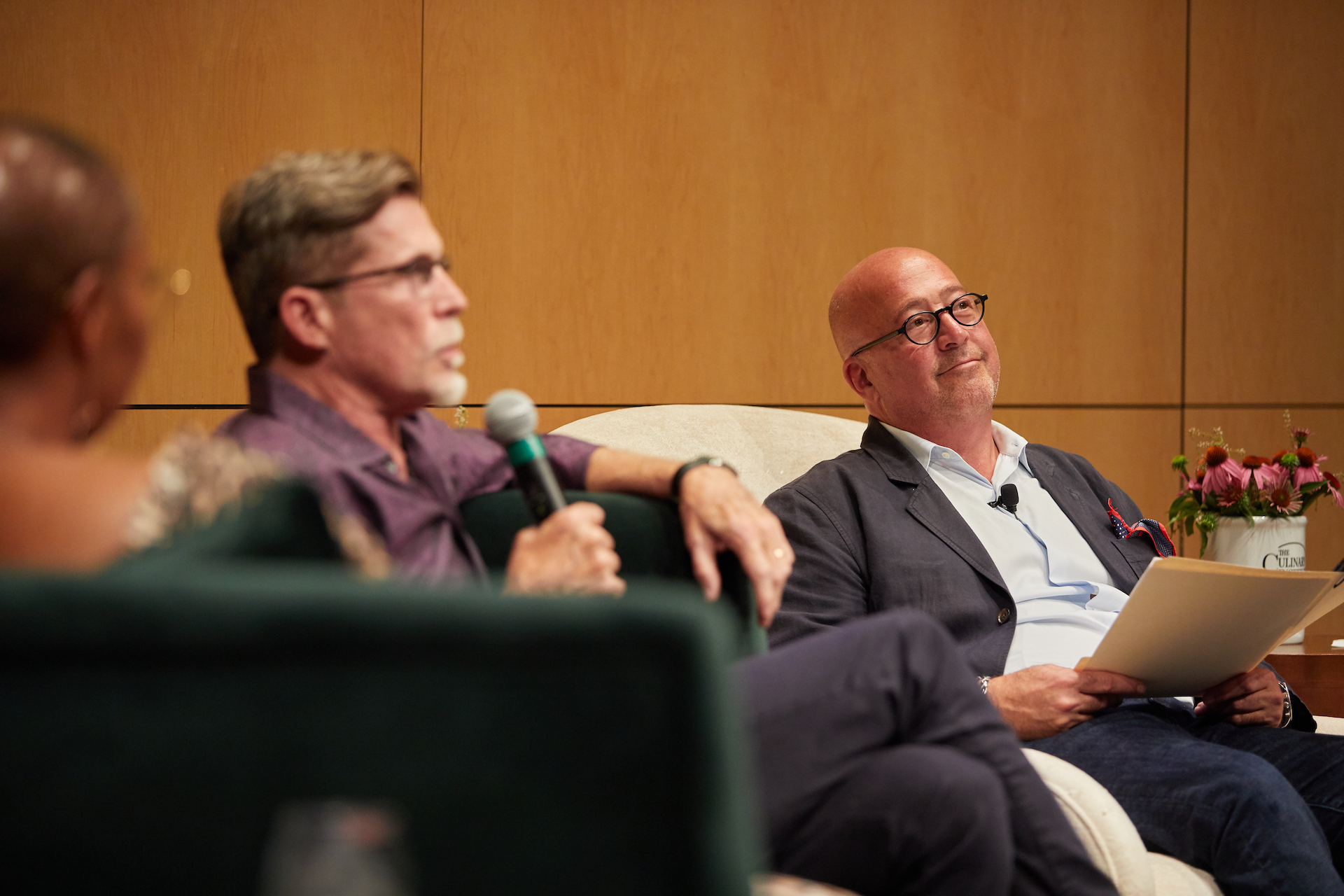 Andrew Zimmern listens on as Rick Bayless answers a question from the crowd.