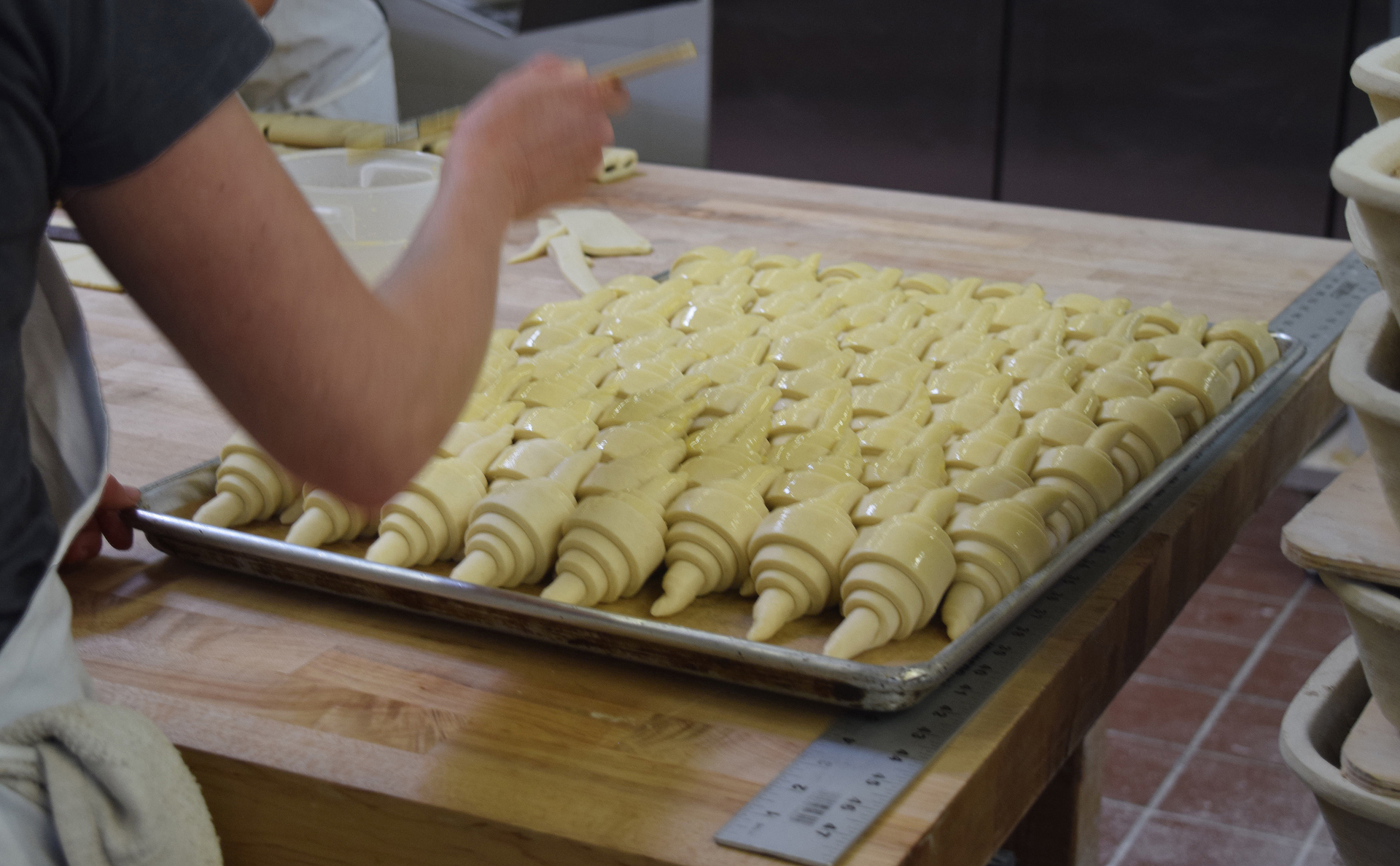 Picture-perfect croissants are buttered before baking. About 70% of bakery revenues currently come from pastries.