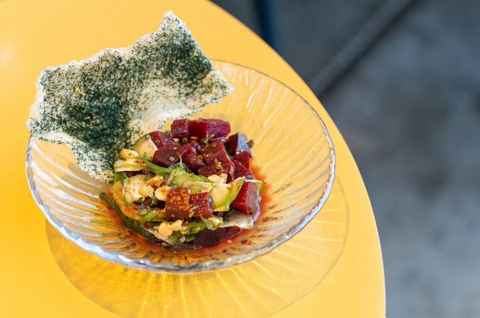 Cubes of chilled beets are topped with slices of cucumber, macadamia crumbles, a dash of ponzu, and sesame seeds, paired with seaweed crackers.