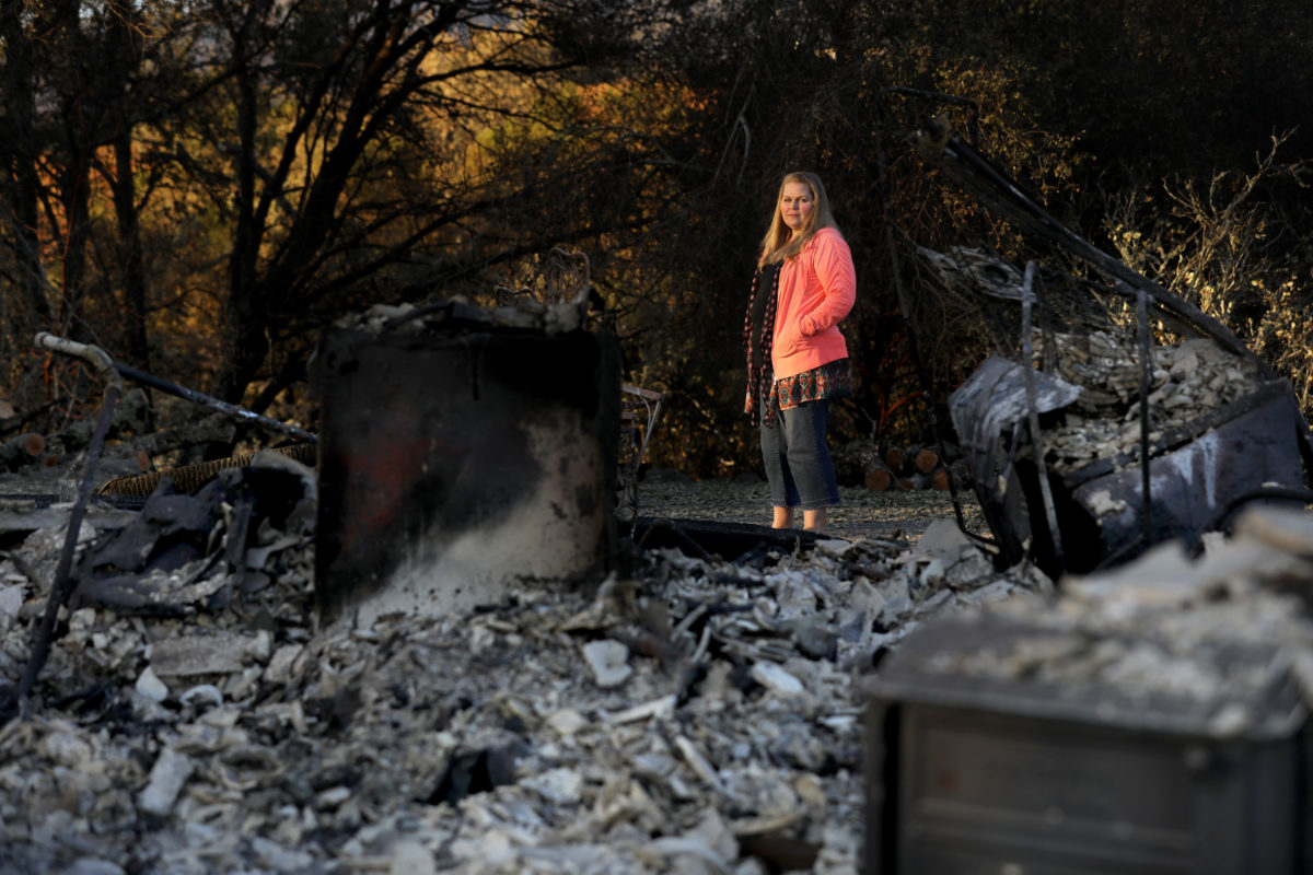 Meghan Dixon stands next to the ruins of her rental home on Hwy 128 in Healdsburg after it burned in the Kincade fire. Photo taken on Monday, November 4, 2019.