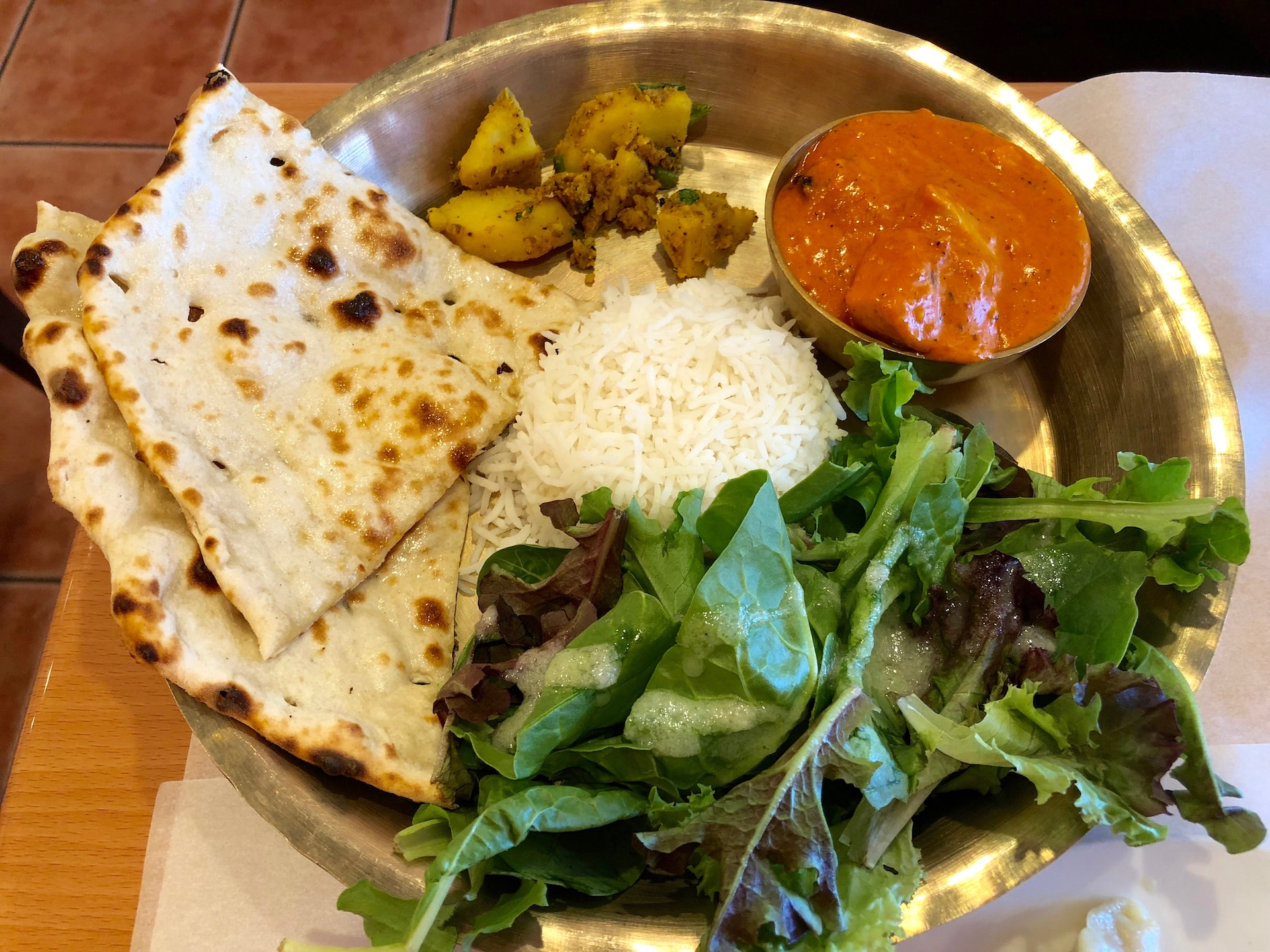 Cuisine of Nepal's signature chicken and cashew cream curry, served as a thali platter at lunch