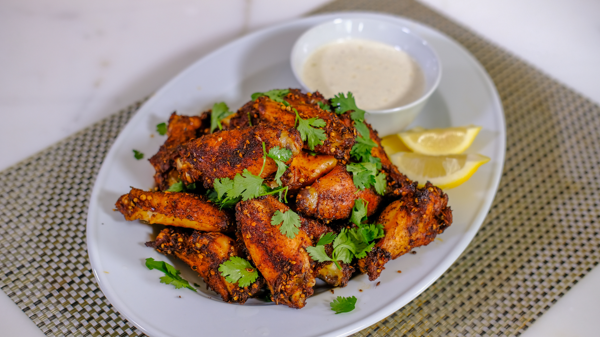 Dry rubbed Harissa Wings paired with lemon and Alabama White BBQ Sauce