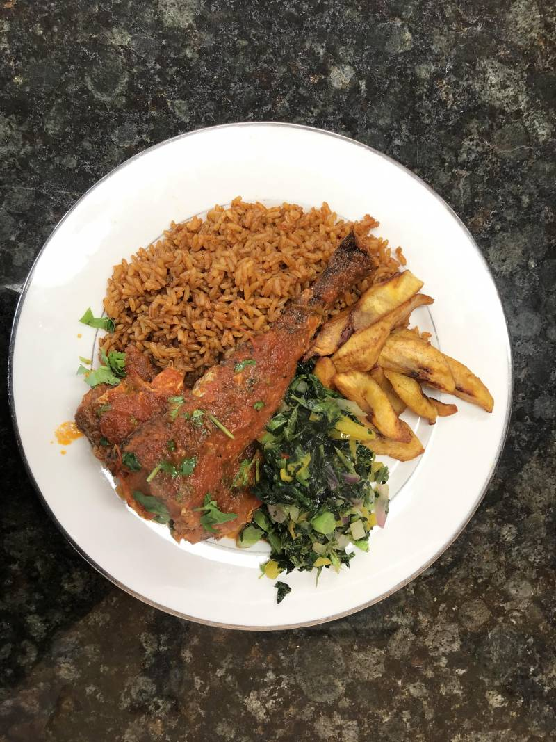 A Jollof rice and plantain plate with tender greens and a fish to top it all of at Ruth's Buka.