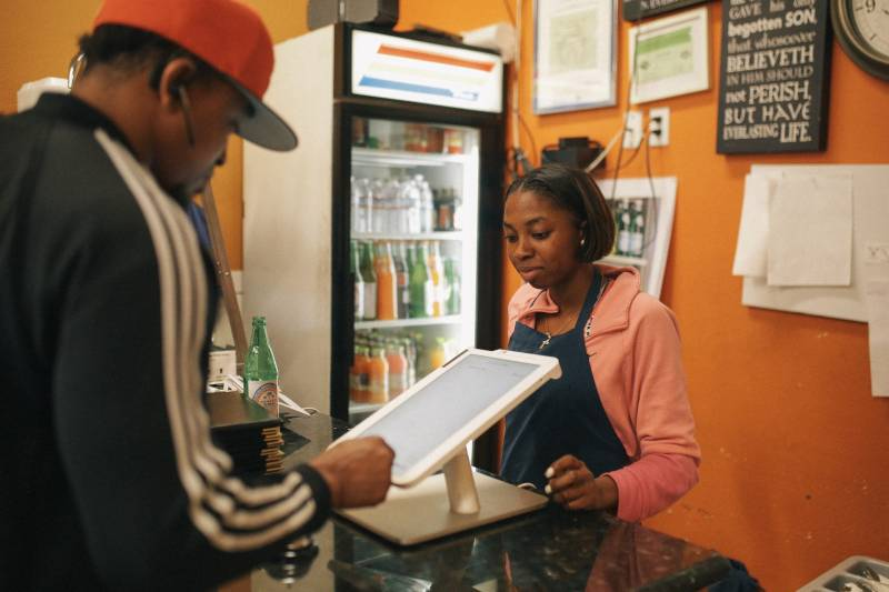 Ruth Ogbe's daughter, Deborah, helps a customer at the family run Oakland restaurant.