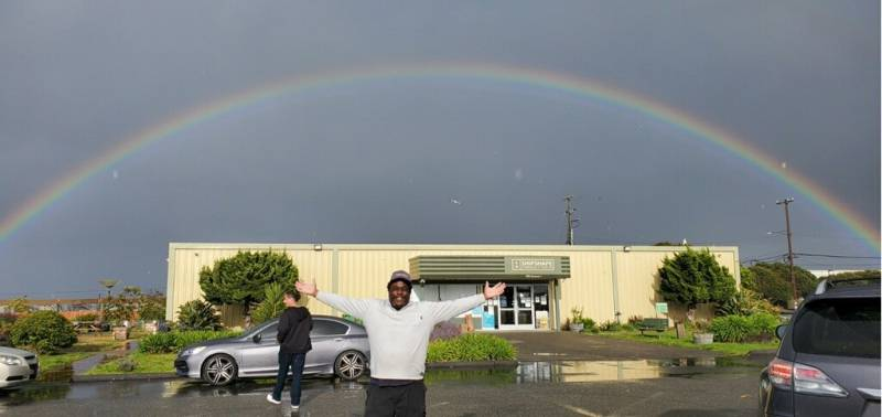 man poses in front of a rainbow