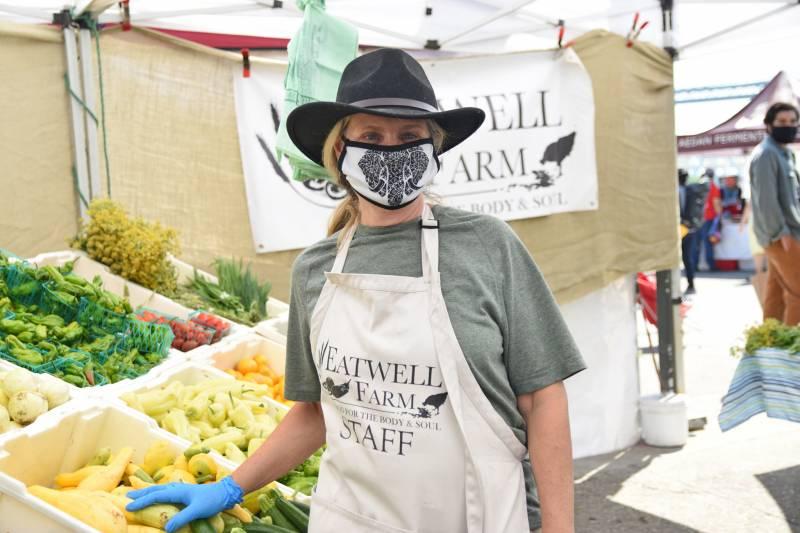 Female farmer wearing a mask at a farmers market