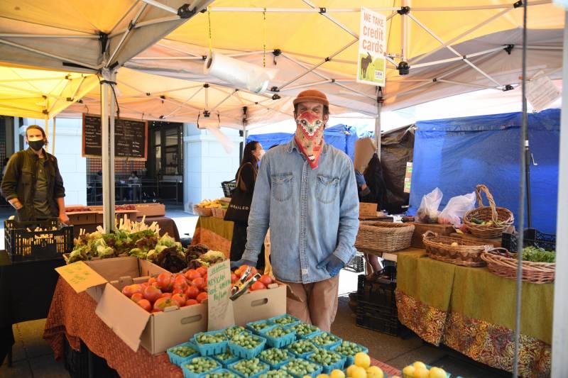 Farmer wearing a mask at a farmers market