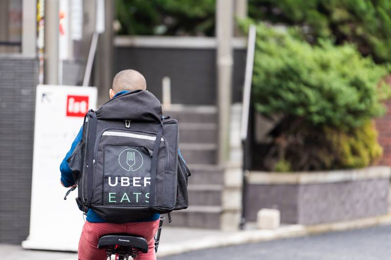 Tokyo, Japan - March 30, 2019: Shibuya street road with back of young delivery man on bicycle for uber eats