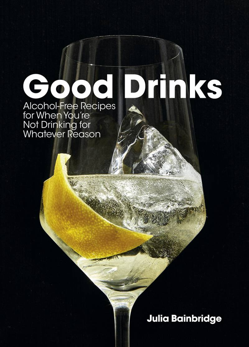 Stemmed glass wtih an ice cube, clear liquid and a lemon peel on a black background. Book cover for Good Drinks