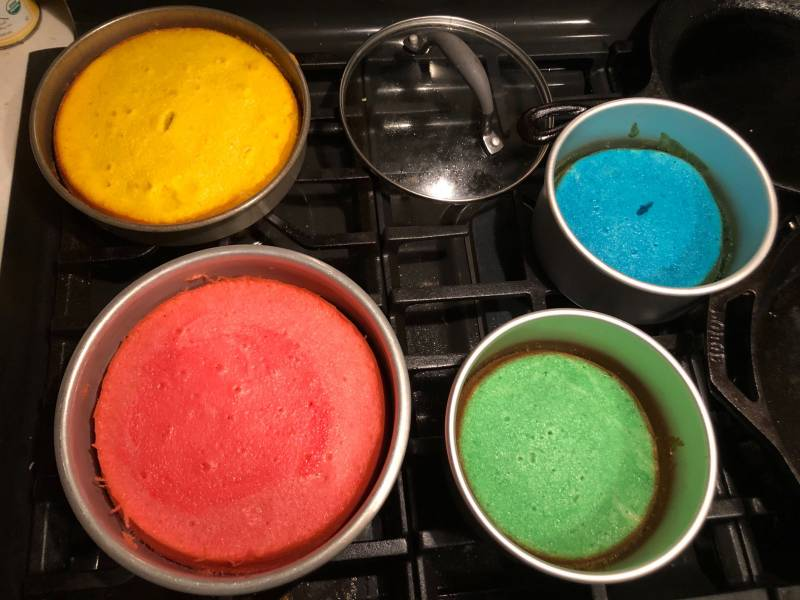 Cake tins on a stove with different colors. One is yellow, one is res, one is green and one is blue. There is also a pot lid on the stove