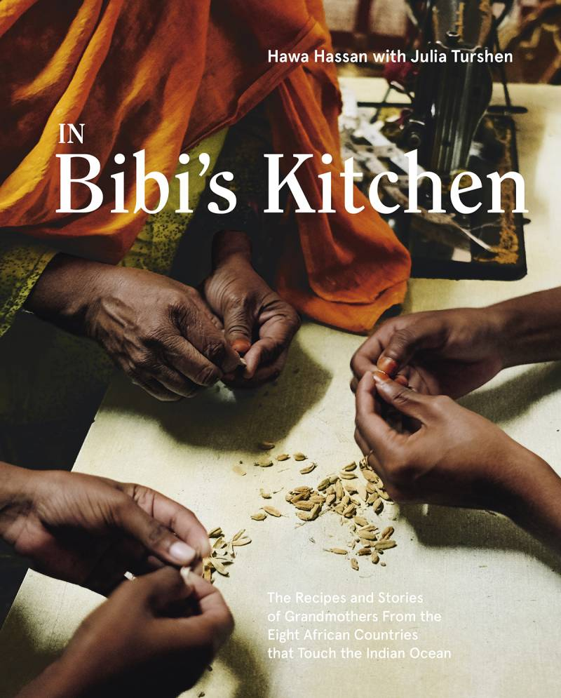 Three hands deseeding something on a table. Book cover for In Bibi's Kitchen