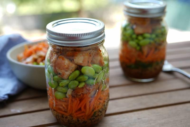 mason jars with quinoa, edamame, carrots and tofu in tem
