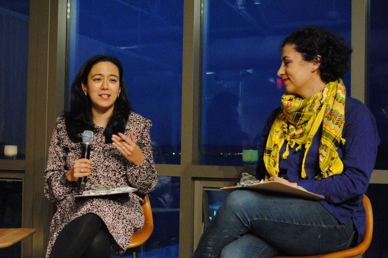 Two women sitting and talking with microphones