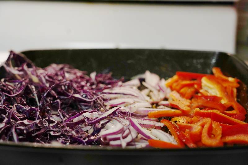 Cabbage, purple onions and bell peppers on a grill pan