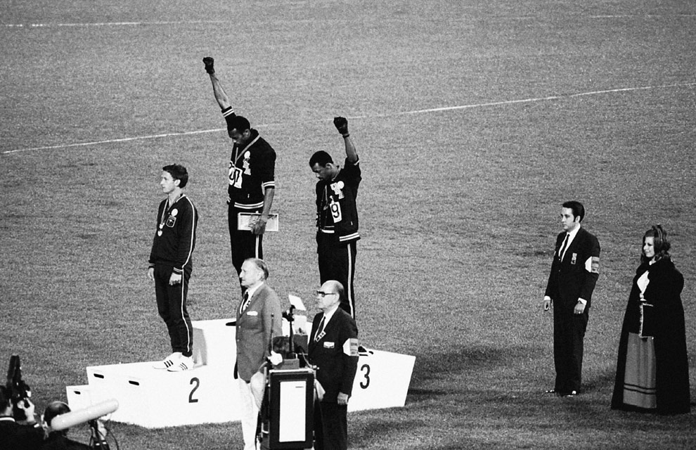 During the medals ceremony at the 1968 Summer Olympics in Mexico City, U.S. track stars Tommie Smith (center) and John Carlos (right) unexpectedly give the Black Power salute. Associated Press