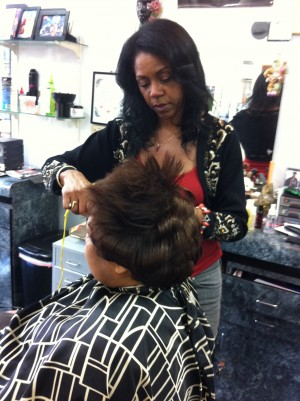 Patricia Davis straightens a clients hair at her salon in Oakland.