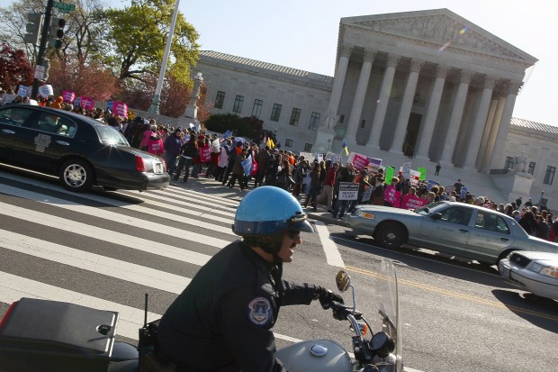 Protesters demonstrate in front of the Supreme Court on the second day of hearings about the constitutionality of the federal health care law. (Mark Wilson: Getty Images)