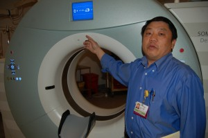 Changvang Her demonstrates how a CAT Scan machine at Mercy Medical Center plays an automated recording of his voice giving directions in Hmong -- for when he's not around to translate.