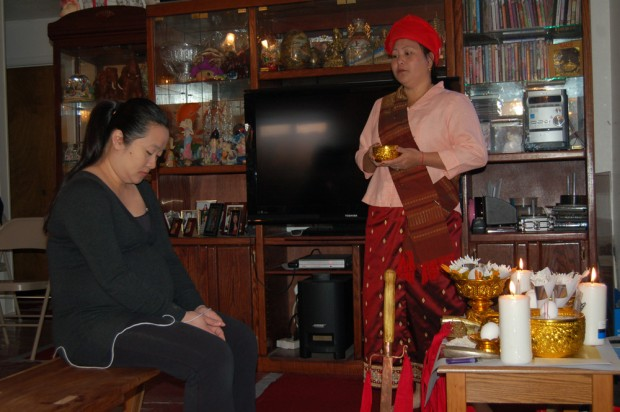 A Hmong shaman blesses a pregnant woman during a traditional healing ceremony.