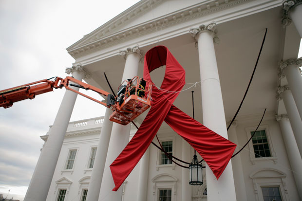 Workers hang a red ribbon on the White House before World AIDS Day, 2011. Chip Somodevilla/Getty Images