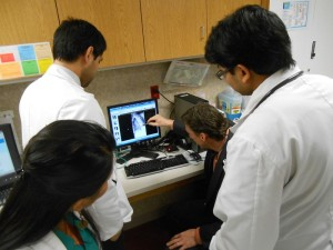 Dr. Peter Broderick examines a patient's x-ray while family practice medical residents look on. (Rebecca Plevin/KVPR)