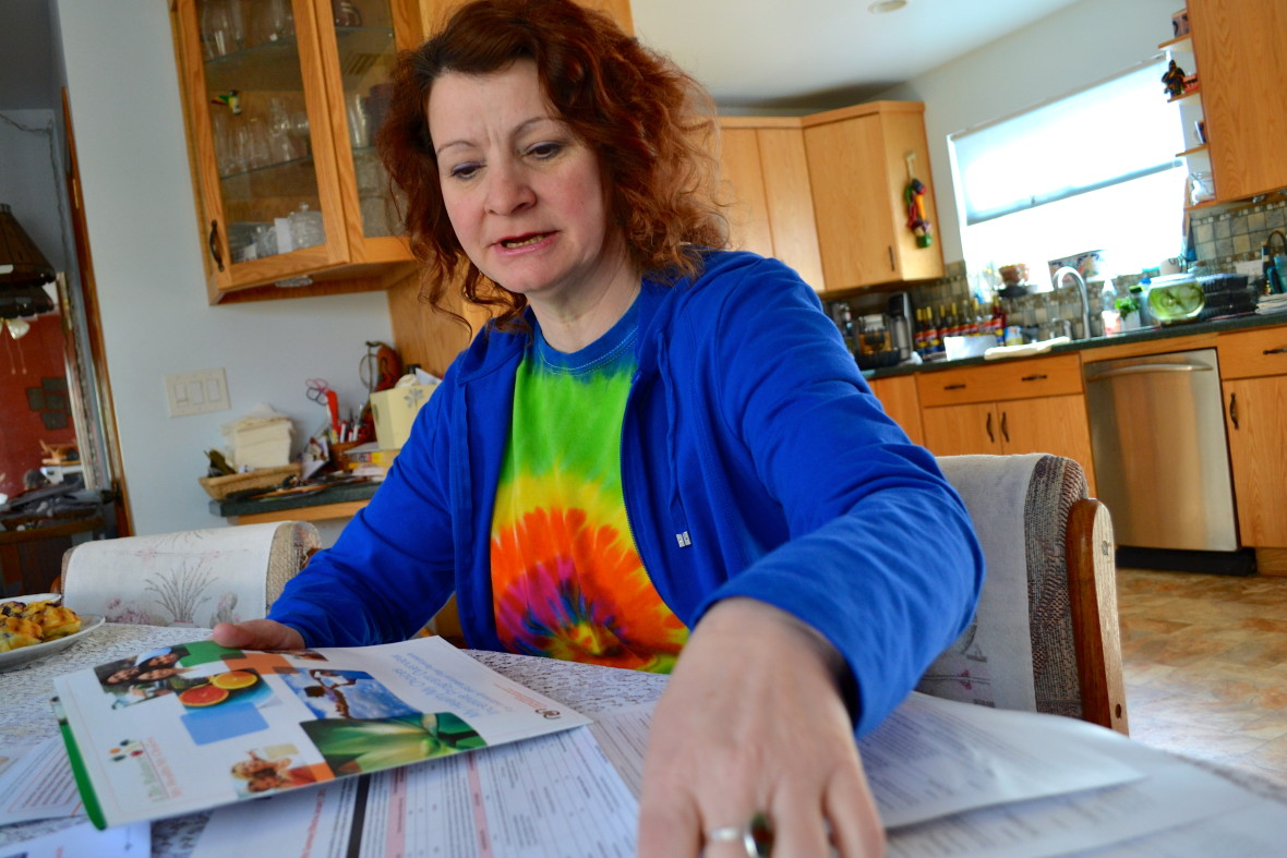"""Kimberley Macgregor, a bookkeeper at a Burbank Ralphs, looks over which """"healthy activities"""" she'll do to offset her health care costs. She says she didn't know about the new wellness program until KQED contacted her. (Photo: Kelley Weiss)"""