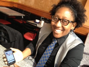 Tamika Butler shows off a mobile app that explains the federal health law's benefits for young people. Butler runs the California chapter of Young Invincibles, an advocacy group. (Mina Kim/KQED)