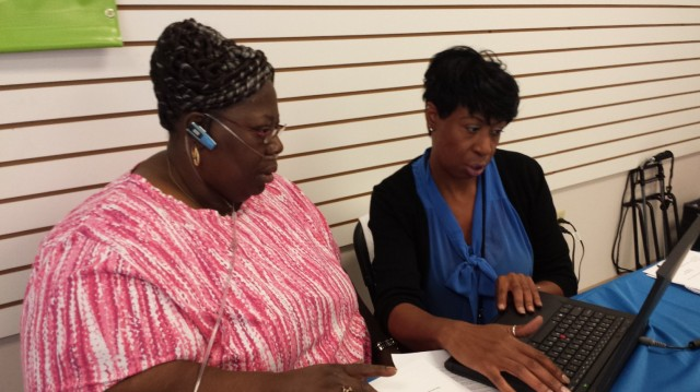 Onita Sanders, a certified application counselor at the Southeastern Virginia Health System, tries to helps Brenda Harrell enroll in health coverage at Enrollfest in Hampton, Va. (Jenny Gold/KHN)