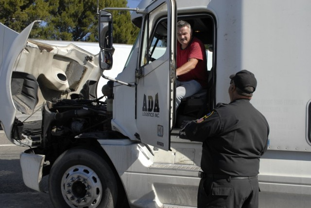 California Air Resources Board field representative Barry Pratt (right) questions Canadian trucker Henry Gustof, left, as a CARB team inspects trucks for compliance with clean air rules at a weighing station north of Los Angeles. Gustof's engine met CARB standards. (Chris Richard/KQED)