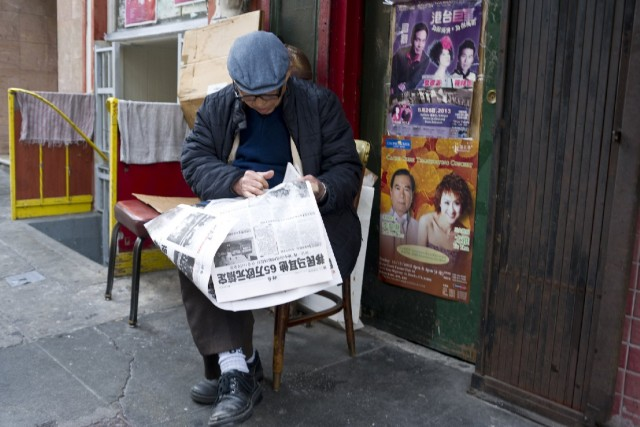 A man reads a Chinese-language newspaper in San Francisco's Chinatown. In the 19th century, the Chinese community was often excluded from mainstream healthcare, and in response, it founded its own Tung Wah medical dispensary. That grew into Chinese Hospital, and later, into CCHP. (Marcus Teply/KQED)