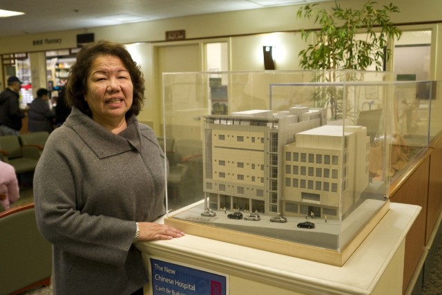 "Chinese Community Health Plan CEO Brenda Yee shows visitors a model of the new Chinese Hospital building. ""We know where our culture, we know where our foundation, where everything started,"" she says. ""We won't lose our identity."" (Marcus Teply/KQED)"