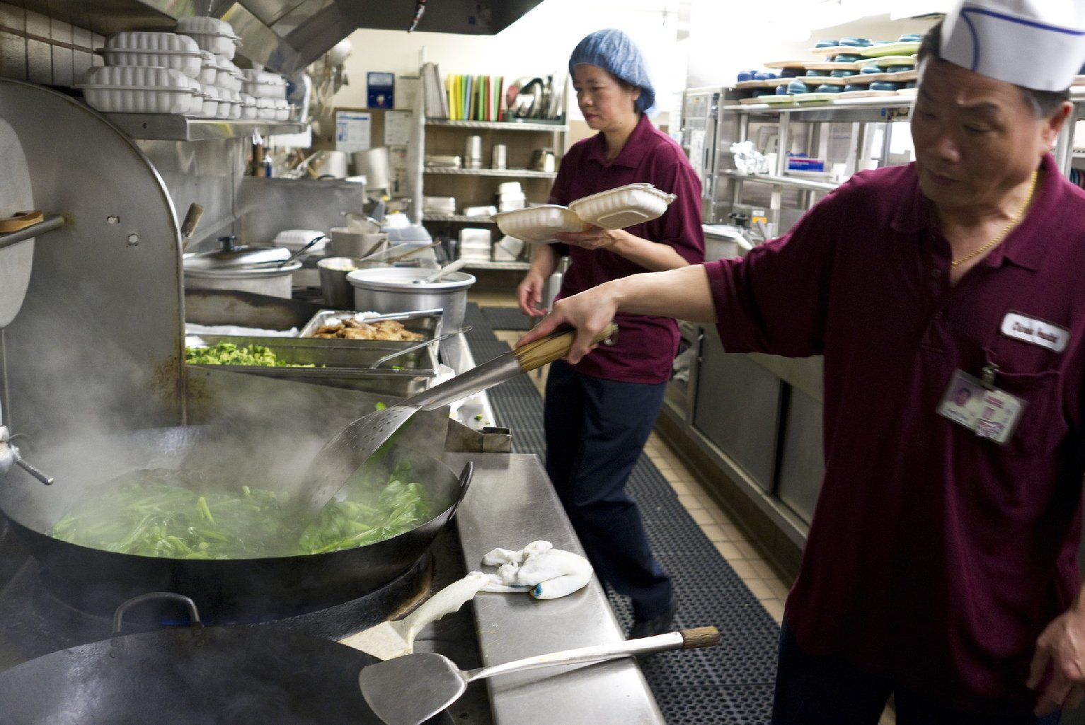 "Cooks in the Chinese Hospital kitchen stir-fry Chinese broccoli. The hospital and its CCHP health plan focus on ""culturally competent"" care for Chinese-American patients; that includes Mandarin- and Cantonese-speaking doctors, coverage for some Eastern medicine, and Chinese hospital food. (Marcus Teply/KQED)"