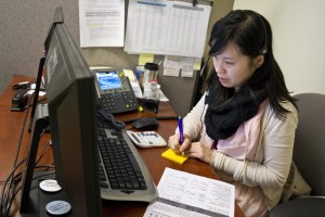 CCHP enrollment counselor Kristen Chow explains Covered California and federal subsidies to a Chinese-language caller. Currently, more than 90 percent of the HMO's members are ethnically Chinese. (Marcus Teply/KQED)