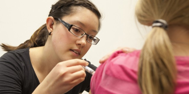 Nursing student administers flu shot. (queensu/Flickr)
