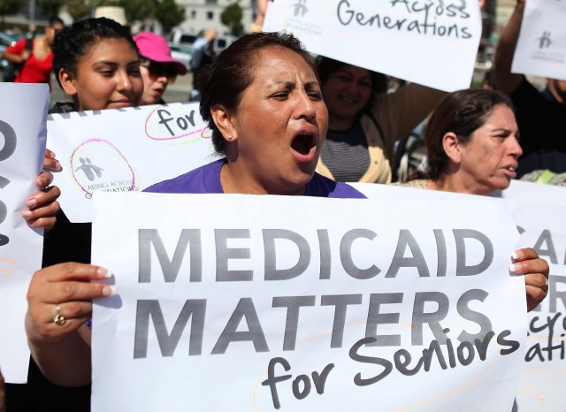 Protestors carry signs against proposed Medi-Cal cuts outside San Francisco city hall in  2011 in San Francisco. (Justin Sullivan/Getty Images)