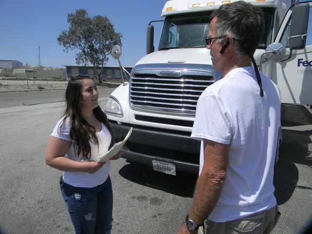 Theresa Moreno, 15, talks to a trucker about strategies to reduce pollution. (Alice Daniel/KQED)