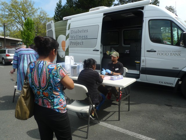 Morgan Smith, a registered nurse with the Redwood Empire Food Bank Diabetes Wellness Project, conducts free diabetes screenings once a month at the Graton Day Labor Center.  The center serves as a conduit between its members -- many of whom are undocumented -- and health organizations around the region. (Lisa Morehouse/KQED)