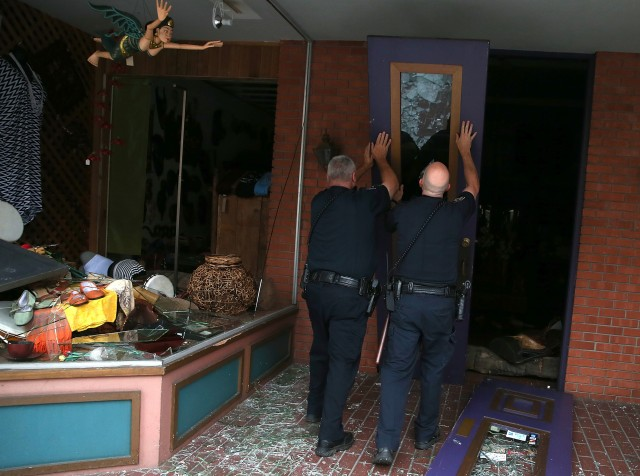 Police officers in Napa prop up a fallen door in front of a damaged building following Sunday's earthquake there. (Justin Sullivan/Getty Images)
