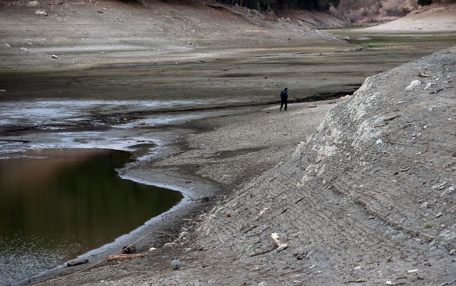 A security guard walks the perimeter of the Almaden Reservoir on January 28, 2014 in San Jose, California. Now in its third straight year of drought conditions, California is experiencing its driest year on record, dating back 119 years, and reservoirs throughout the state have low water levels. Santa Clara County reservoirs are at 3 percent of capacity or lower. California Gov. Jerry Brown officially declared a drought emergency to speed up assistance to local governments, streamline water transfers and potentially ease environmental protection requirements for dam releases. (Photo by Justin Sullivan/Getty Images)