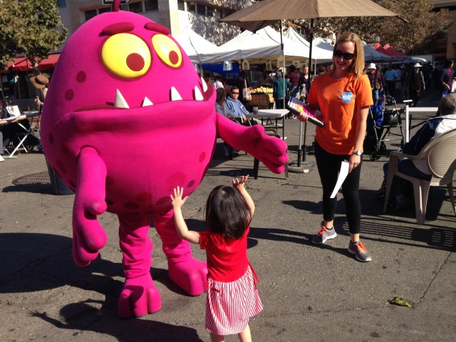 The Shoo the Flu mascot helps spread the word on the importance of the flu vaccine at the Old Oakland Farmers Market earlier this month. (Lisa Alifers/KQED)
