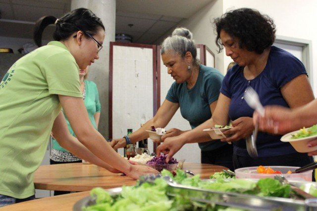 "Fresh Approach staffers chop a variety of fruits and vegetables for today's summer salad. ""We tried to choose one of every color,"" says Laura deTar, Nutrition Program Manager for Fresh Approach. ""We want to expose people to things they may not have had."" (Brittany Patterson, KQED)"