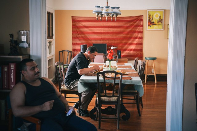 Jarrar at his transitional housing in West Oakland, eating fried potatoes and eggplant from a charity food table in the neighborhood.