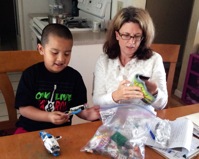 Sarah Boone, a behavior analyst with the social services agency EMQ FamiliesFirst, evaluates Ernesto Santiago, 6, of San Jose for autism therapy services. (Barbara Feder Ostrov/Kaiser Health News)