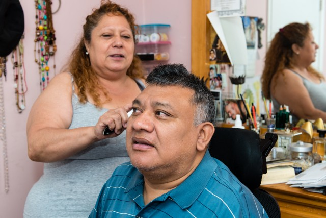 Frances Chuc brushes her husband's hair. Jorge Chuc has been paralyzed for more than 30 years and needs full-time care from his wife. (Heidi de Marco/KHN)