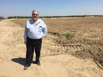 Respiratory therapist Kevin Hamilton stands near an unplanted field on a dusty farm road west of Fresno.