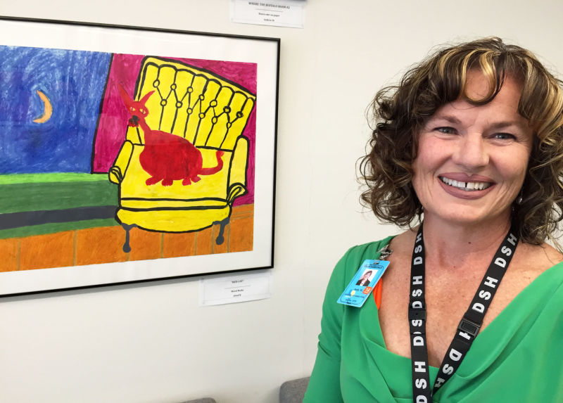 Dolly Matteucci became executive director of Napa State Hospital after Donna Gross's murder. She stands in a conference room decorated with paintings created by psychiatric patients.