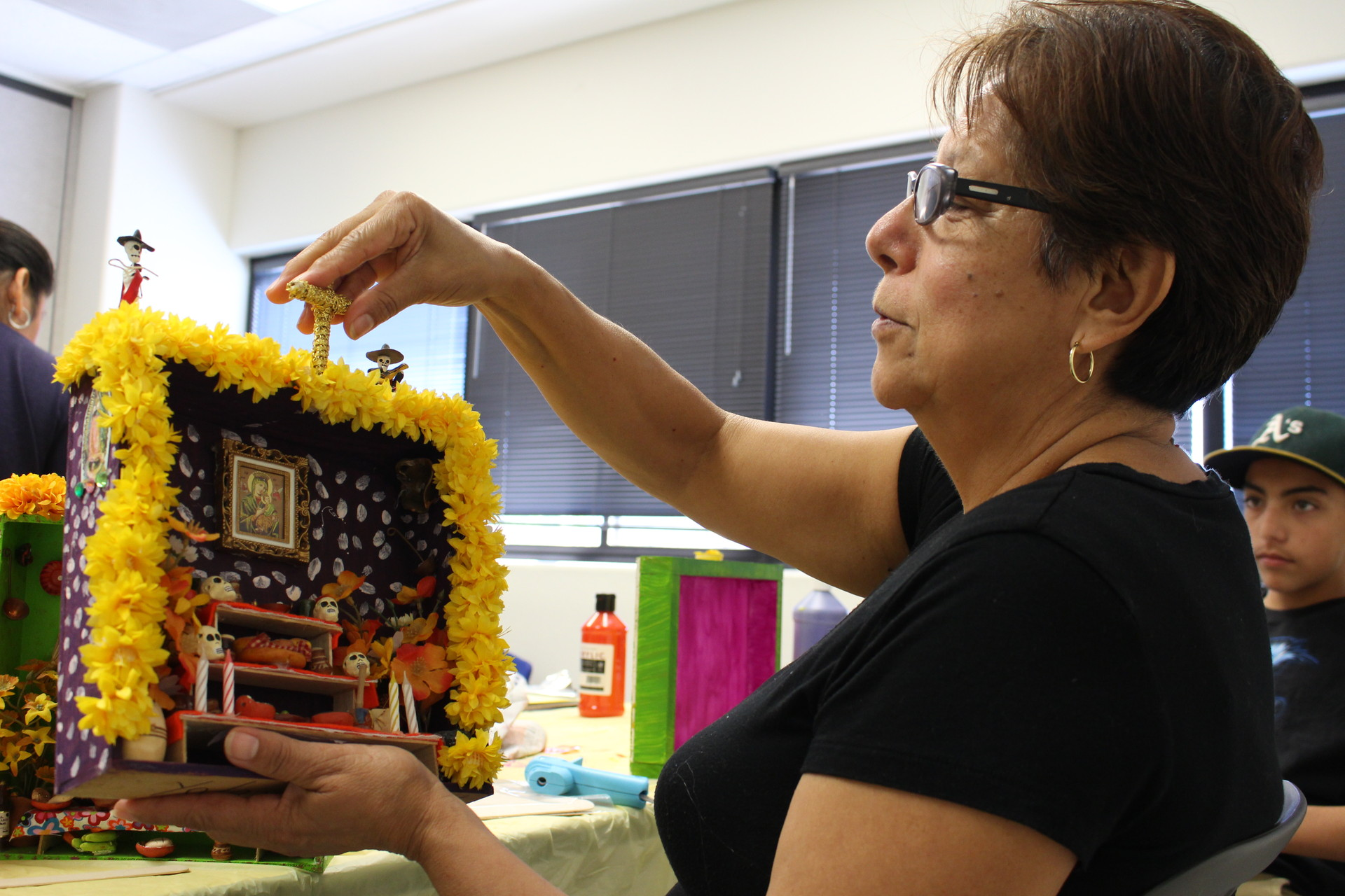 Yolanda Tell shows off a nicho she made for her daughter, as grandson Victor Hugo Perez looks on. Tell's daugher died in a car accident when Perez was 3 years old. Tell takes care of him and his brother.