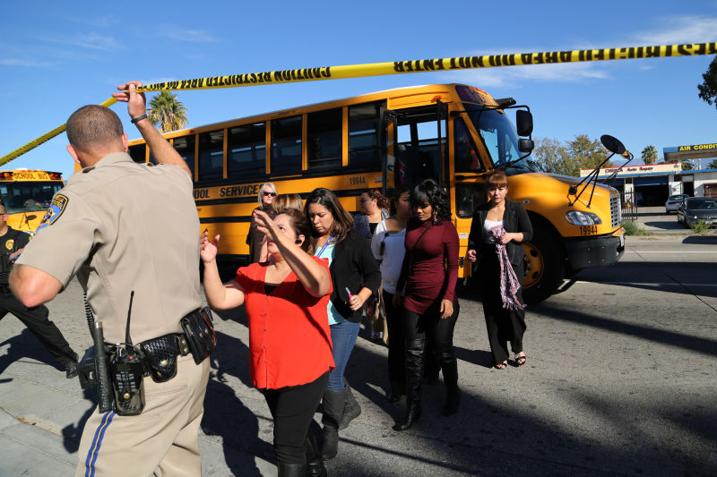 Employees and other people are evacuated by bus from the site of a mass shooting at the Inland Regional Center in San Bernardino.